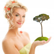Beautiful young woman holding pine-tree — Stock Photo