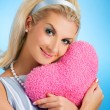 Beautiful woman with fluffy heart pillow — Stock Photo