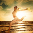 Beautiful woman jumping on a beach - Foto Stock