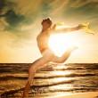 Beautiful woman jumping on a beach — Stock Photo