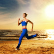 Beautiful woman running on a beach - Stok fotoğraf