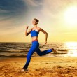 Beautiful woman running on a beach - Stockfoto