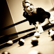 Beautiful woman playing billiards - Stock Photo