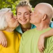 Grandparents kissing their granddaughter - Stock Photo