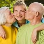 Grandparents kissing their granddaughter — Stock Photo
