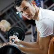 Handsome man lifting weight in a gym - Stock Photo