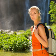 Tourist with backpack near waterfall — Stock Photo