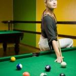 Beautiful blond woman playing billiards — Stock Photo