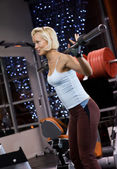 Strong beautiful woman lifting heavy weights — Stok fotoğraf