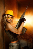Beautiful woman with heavy drill — Stock Photo