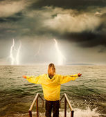 Brave woman greeting stormy ocean — Stock Photo