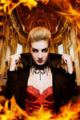 Female vampire in a burning church — Stok fotoğraf