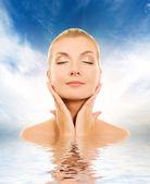 Beautiful woman massaging her face — Stock Photo