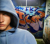 Hooligan in a graffiti painted gateway — Stock Photo