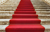 Ancient stairs covered with red carpet — Stock Photo
