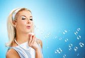Beautiful woman blowing soap bubbles — Stock Photo