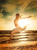 Beautiful woman jumping on a beach — Stock Photo