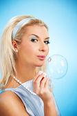 Beautiful woman blowing soap bubble — Stock Photo