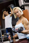 Strong woman lifting heavy dumbbells — Stock Photo