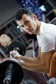 Handsome man lifting weight in a gym — Stock Photo