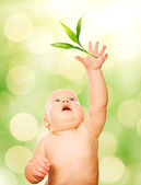 Beautiful baby trying to catch green leaf — Stock Photo
