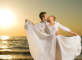 Couple in love on a beach at sunset — Stock Photo