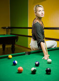 Beautiful blond woman playing billiards — Stock Photo