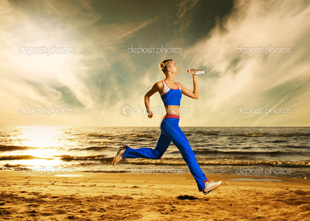 Beautiful young woman running on a beach at sunset — Stock Photo #2085318