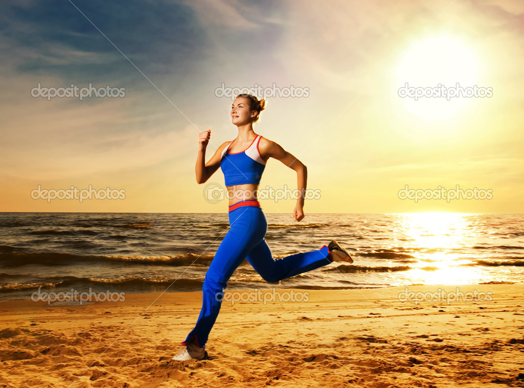 Beautiful young woman running on a beach at sunset — Lizenzfreies Foto #2085738