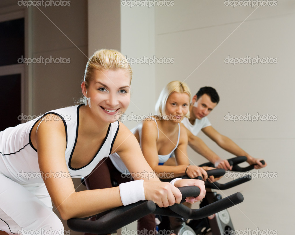 Group of doing exercise on a bike in a gym — Stock Photo #2085859