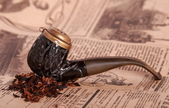 Tobacco pipe on old paper — Stock Photo