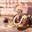 Chest with jewelry on antique map — Stock Photo
