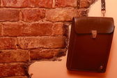 Leather bag hanging on brick wall — Stock Photo