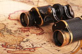 Old binoculars on antique map — Stock Photo