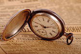 Pocket watch on vintage newspaper — Stock Photo