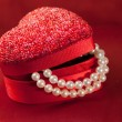 Red heart gift box with string of pearls — Stock Photo #1910111