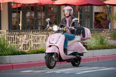 Lady biker zipping along on her pink sco — Stock Photo