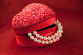 Red heart gift box with string of pearls — Stock Photo