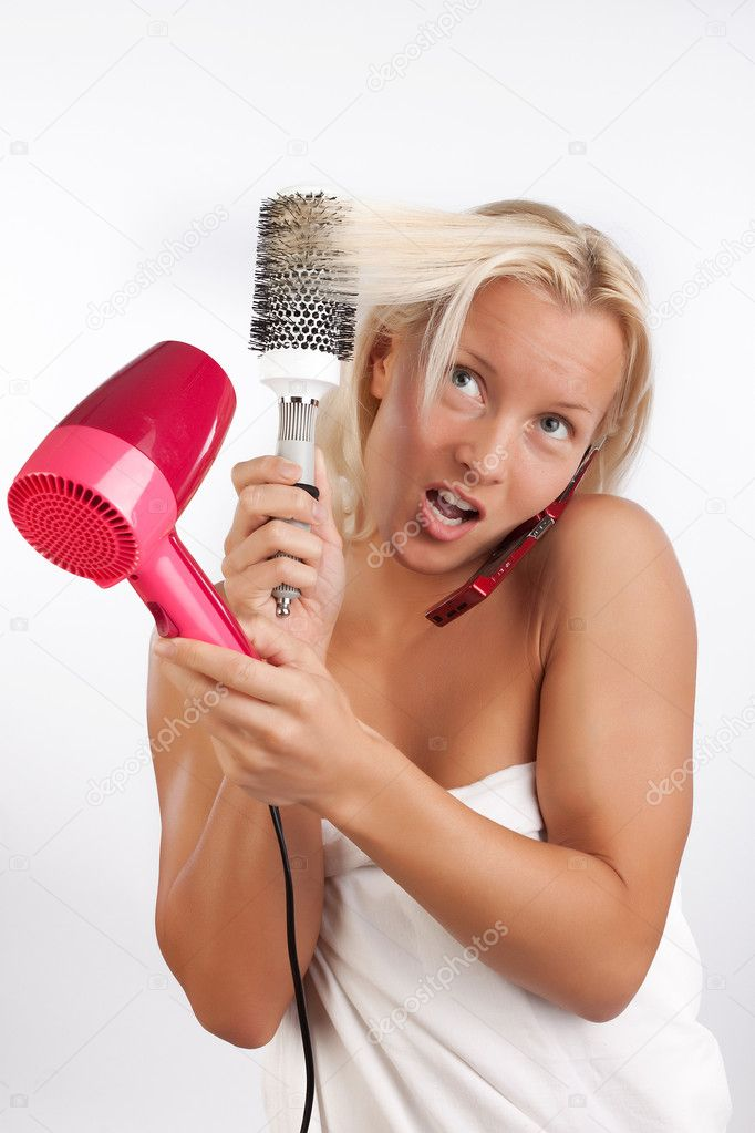 Portrait of attractive woman drying her blond hair with hairdryer and talking by cellphone  Stock Photo #1401860