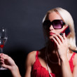 Blond woman with phone and glass — Stock Photo