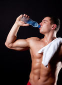 Athlete drinking mineral watet — Stock Photo