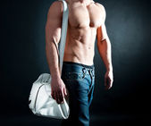 Man with athletic body holding a bag — Stock Photo