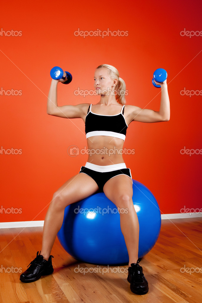 Beautiful blond athlete sitting on fitness ball with dumbbells  Foto Stock #1586486