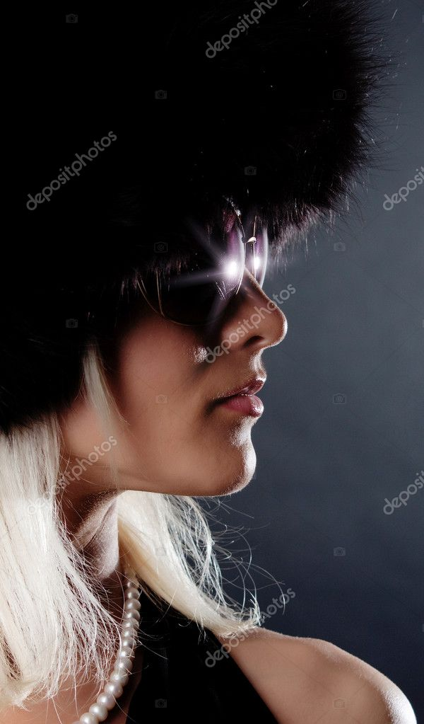 Sexy blonde wearing fur cap and shining sunglasses — Stock Photo #1876382