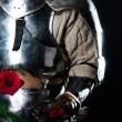 Knight looking at beautiful rose — Stock Photo