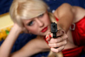 Woman holding gun, focus on gun — Stock Photo
