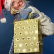 Blonde girl in santa hat with gift bag — Stockfoto