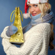 Blonde girl in santa hat with gift bag — Stock Photo