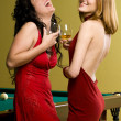 Two beautiful girls in red with cognac — Stock Photo