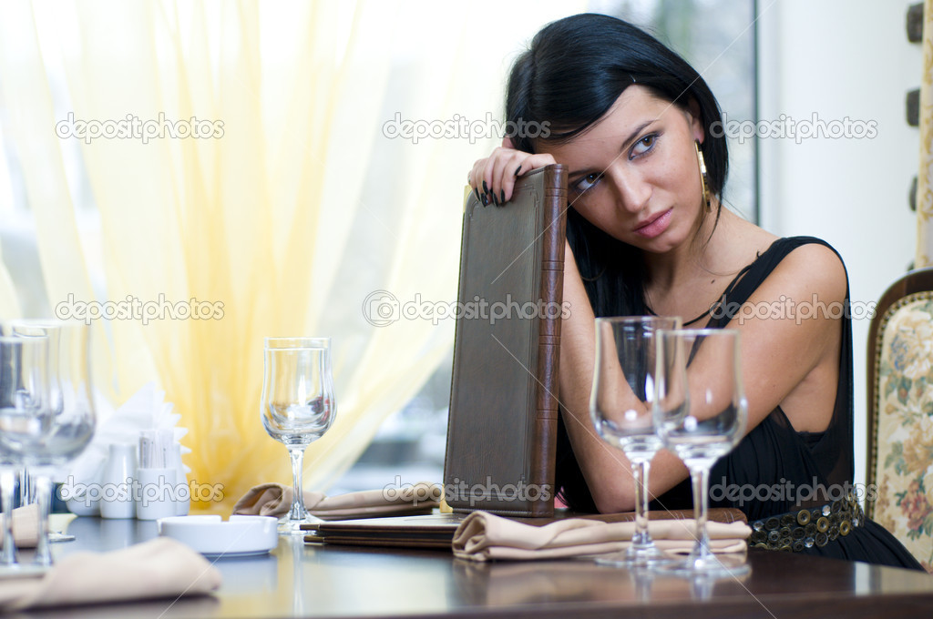 Beautiful woman dressed gown is sitting in restaurant and keeping menu — Photo #1616630